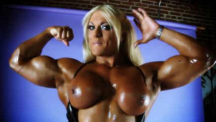 Female bodybuidler Lisa Cross flexing thick biceps