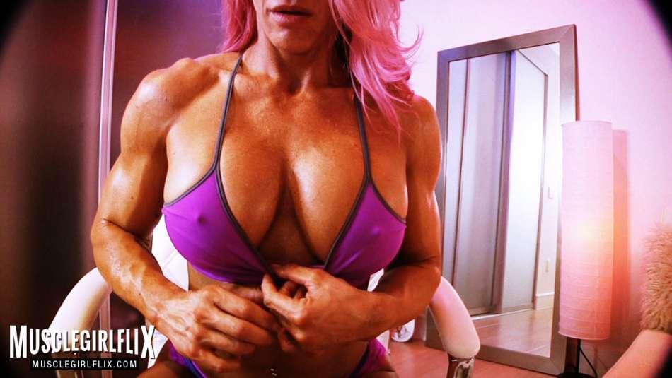 muscular female bodybuilder flexing on webcam