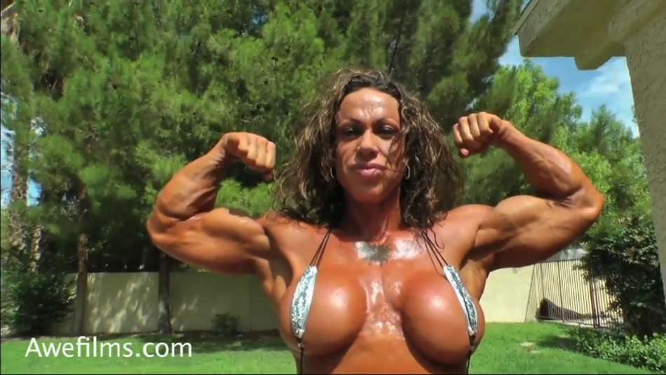 female bodybuilder flexing biceps and big tits