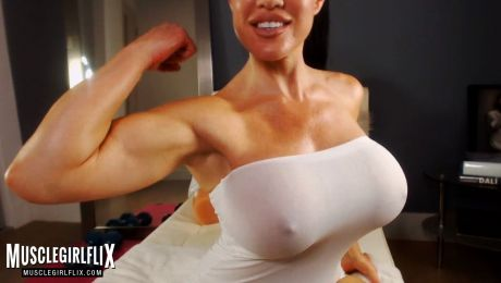 Busty webcam model Samantha Kelly flexing her bicep.