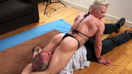 female bodybuilder crushing a guy with muscular legs
