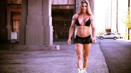 Maria Garcia showing off her muscle under a bridge.