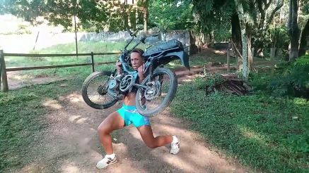 strong girl lifting a motor bike
