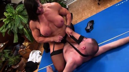 muscular woman dominating a weak man