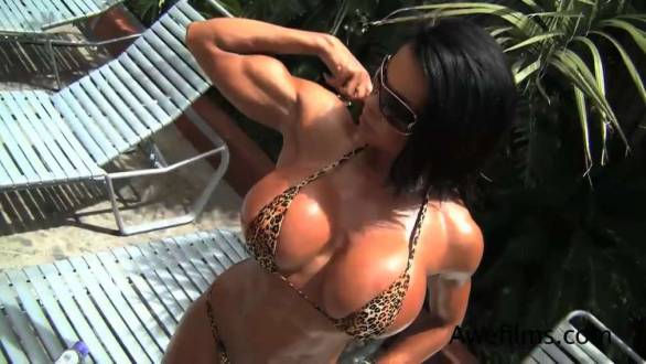 fitness model showing off huge fake tits in a tiny bikini