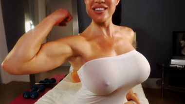 Busty webcam model Samantha Kelly flexing her bicep.